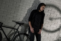 Sometimes you just want to be alone. Shot of a young man wearing black and standing against a brick wall Royalty Free Stock Photo