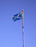 Somewhat frayed Scottish flag on rusty flagpole Stock Photos