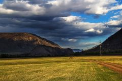 Rainy clouds over sunlighted valley. Somewhere deep within Altai mountains, Russia Stock Images