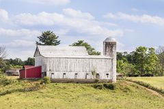 Somewhere in Ohio. A large white cattle barn with silo stands on a hilly Ohio farm under a cloudy blue sky Royalty Free Stock Photo
