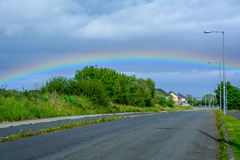 Somewhere over the rainbow. Kilcoole landscape, Wicklow county, Ireland. Colorful rainbow on a cloudy sky above Kilcoole street Royalty Free Stock Images