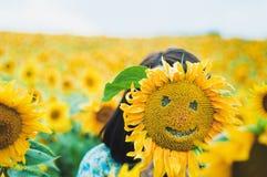 Somewone het verbergen achter de het glimlachen zonnebloem Stock Foto