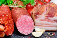 Somked sausages with colorful peppercorns, tomatoes and garlic Stock Images