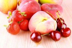 Sommar bär frukt - körsbär, jordgubbar, persikor, äpplen och mango royaltyfri bild