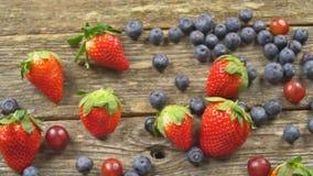 Sommar bär frukt på en trätabell Video för hd för ULTRARAPID för blåbärdruvajordgubbar arkivfilmer