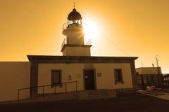 Sommar: en fyr med solnedgångljus av udde av korsen i Spanien Royaltyfri Fotografi