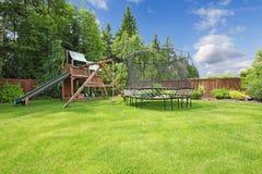 Sommar fäktad trädgård med spelrumområde. royaltyfria foton