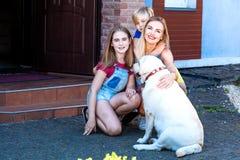 Sommar för gräs för husdjuret för solen för labradormoderdottern parkerar den hem- solen som skrattar blond tonåringspädbarnsomma royaltyfria bilder