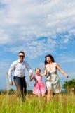 sommar för lycklig äng för familj running Arkivfoton