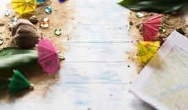 sommar för snäckskal för sand för bakgrundsbegreppsram Paraplyer för coctailar på sand på en träbakgrund med kiselstenar Arkivfoton