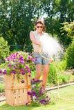 sommar för trädgårds- slang för blomma som le bevattnar kvinnan Royaltyfria Foton