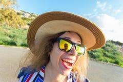 Sommar-, ferie-, selfie- och semesterbegrepp - ung kvinna som gör den roliga framsidan på den bärande hatten och solglasögon för  Arkivfoton