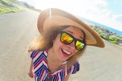 Sommar-, ferie-, selfie- och semesterbegrepp - ung kvinna som gör den roliga framsidan på den bärande hatten och solglasögon för  Royaltyfria Bilder