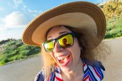 Sommar-, ferie-, selfie- och semesterbegrepp - ung kvinna som gör den roliga framsidan på den bärande hatten och solglasögon för  Arkivbilder