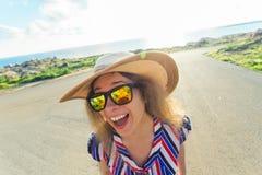 Sommar-, ferie-, selfie- och semesterbegrepp - ung kvinna som gör den roliga framsidan på den bärande hatten och solglasögon för  Arkivbild
