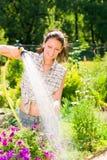sommar för trädgårds- slang för blomma som le bevattnar kvinnan Royaltyfria Bilder