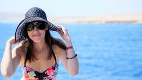Sommar hav, stående av en härlig ung brunettkvinna som bär en baddräkt- och solhatt, solglasögon som står på a stock video