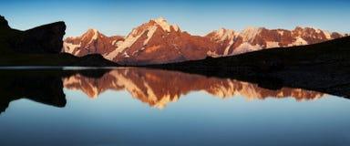Sommar i de schweiziska fjällängarna, Murren område som förbiser Eigeren, reflekterade Monch och Jungfrau berg, i Grauseewli sjön arkivfoto