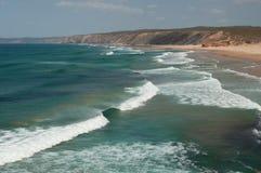 Sommar i den Algarve kusten, Portugal Vaggar i shorelinen och det blåa vattnet Arkivfoton