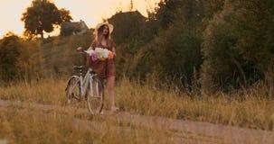 Sommar i fältflickan med blommor och en hatt går med en cykel på vägen stock video