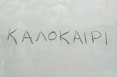 Sommar i grekiskt skriftligt i sanden Arkivbilder