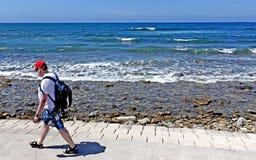Sommar i Italien, går en man med ett rött hat framme av havet royaltyfri foto