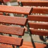 Sommar i staden - regndroppar på trästolar Royaltyfri Foto