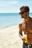 Sommar Idrotts- muskulös man som dricker Juice Cocktail On Beach Royaltyfri Fotografi