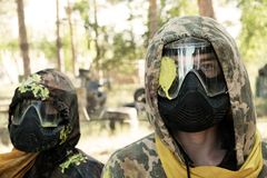 Sommar Paintball Två spelare med ett nederlag i huvudet i en kamouflagedräkt och en skyddande maskering med en gul fläck på arkivbild