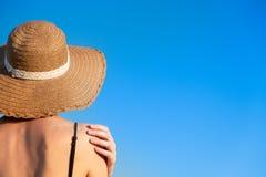 Sommar semestrar lynne: kvinnlig i strandhatten som täckas i sand i ljus blå bakgrund royaltyfri fotografi