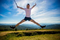 Sommar som fotvandrar i berg Den unga turist- mannen i lock med händer upp av berg beundrar överst naturen royaltyfri foto