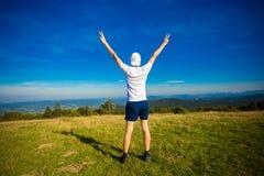 Sommar som fotvandrar i berg Den unga turist- mannen i lock med händer upp av berg beundrar överst naturen arkivbild
