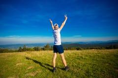 Sommar som fotvandrar i berg Den unga turist- mannen i lock med händer upp av berg beundrar överst naturen arkivfoton