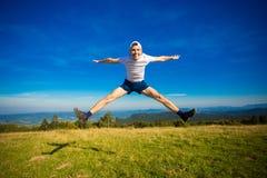 Sommar som fotvandrar i berg Den unga turist- mannen i lock med händer upp av berg beundrar överst naturen royaltyfri bild