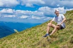 Sommar som fotvandrar i bergen Den unga turist- mannen i ett lock med händer upp på överkanten av bergen beundrar naturen arkivfoto