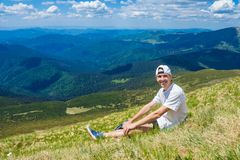 Sommar som fotvandrar i bergen Den unga turist- mannen i ett lock med händer upp på överkanten av bergen beundrar naturen royaltyfria foton