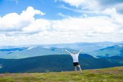 Sommar som fotvandrar i bergen Den unga turist- mannen i ett lock med händer upp på överkanten av bergen beundrar naturen royaltyfri fotografi