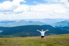 Sommar som fotvandrar i bergen Den unga turist- mannen i ett lock med händer upp på överkanten av bergen beundrar naturen fotografering för bildbyråer