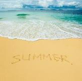 Sommar som skrivs i en sandig strand Arkivbild