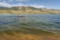 Sommar står upp paddleboard på sjön i Colorado Arkivfoto
