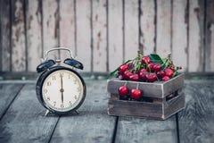 Sommar Tid, röd körsbär och en ringklocka på en gammal trätabell Arkivbild