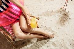 Sommar Tycka om tystnad på stranden, medan dricka den nya kalla coctailen Arkivbilder