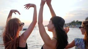 Sommar vilar på solnedgången, gladlynta vänner som dansar på solnedgången på stranden, flickvänlönelyftarmar upp på sjösidan stock video