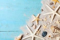 Sommarbakgrund från snäckskal, sjöstjärna och sand på blå bästa sikt för tabell royaltyfri foto