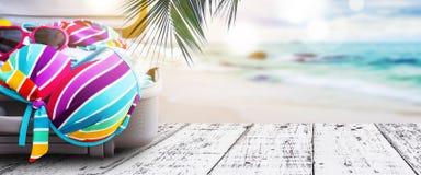 Sommarbegrepp av den färgrika bikinin och kläder i bagage Fotografering för Bildbyråer