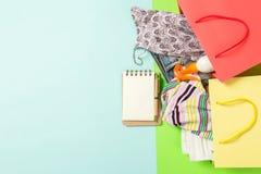 Sommarbegrepp av färgglade shoppa påsar som är fulla av kläder Gåvapåsar med T-tröja, grov bomullstvillkortslutningar, anteckning arkivbild