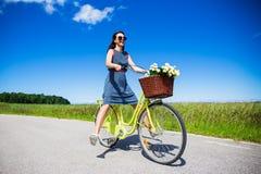 Sommarbegrepp - lycklig rolig ridning för ung kvinna på cykeln arkivfoton