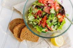 Sommarbegrepp, sallad av grönsallatbladet, tomat, gurka, lök, oreganon med olivolja och citronjuice Royaltyfria Foton