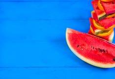 Sommarbegrepp: Skivad vattenmelon på blå lantlig wood bakgrund arkivbild