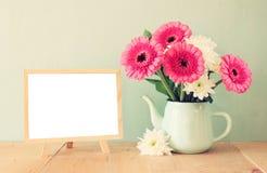 Sommarbukett av blommor på den trätabellen och svart tavla med rum för text med mintkaramellbakgrund tappning filtrerad bild Arkivfoto